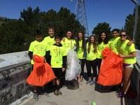 Teens in lime green shirts holding large trash bags.